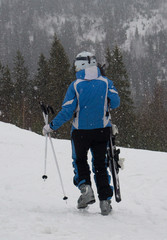 A skier walks down the slope with skis in his hands in the snow