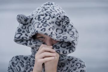 girl wearing a onesie with a hood, peeking