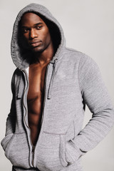Muscular man in hooded sweatshirt looking away in thought