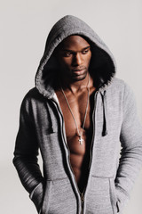 Handsome young man in hooded shirt with bare chest looking away