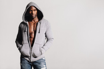 Thoughtful man in hooded sweatshirt with bare chest