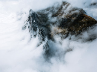 Mountain range in Switzerland cradled with thick clouds during autumn