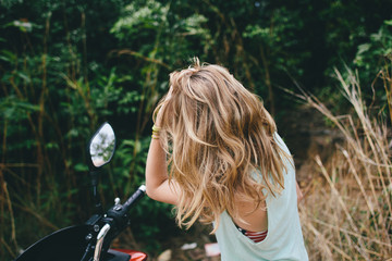 Young girl puts her hair looks in the mirror motorcycle
