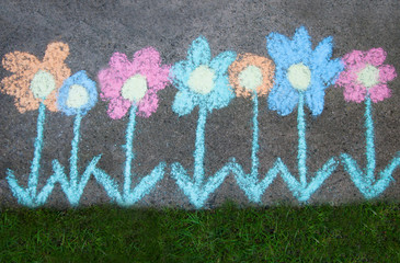 Chalk flowers drawn on pavement next to green grass