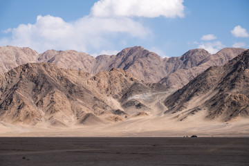 Landscape image of mountains and blue sky background with people and cars in Leh Ladakh , India