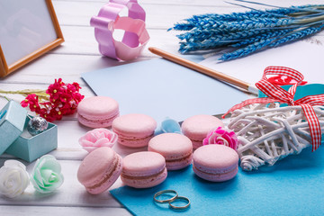 Pink heart shaped macaroons and wedding rings with postcard. place for inscription.