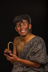 Close up of funny prehistoric smiling to the camera, holding a cellphone and writting with a wood stick, in a black background