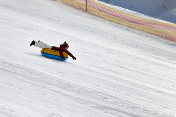 Happy girl downhill on snow tube on ski resort