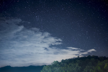 Beautiful night scape with dark blue sky with a lot of star white cloud and the green mountain. View from the village in the forest at the north part of Thailand.