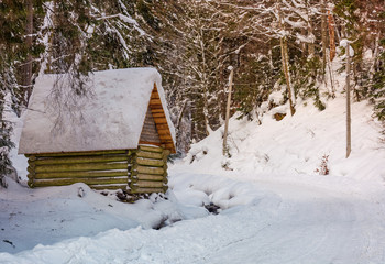 woodshed by the road in winter forest. lovely nature scenery