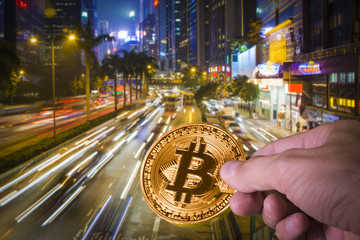 Hand holding a bitcoin with night view of Hong Kong in the background.