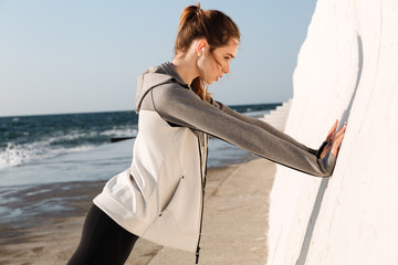 Healthy fit girl doing push-ups while standing near white wall, seaside outdoor