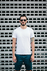 A stylish man with a beard in a white T-shirt and glasses on a city background. Street photo