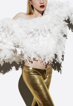 model posing in white feather fashion and golden pants