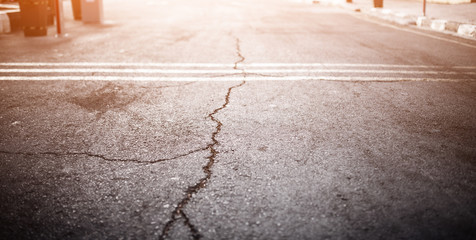 Texture of the old road with cracks. Asphalt surface on the street. Glare of light. Web banner size. 16 in 9 crop.
