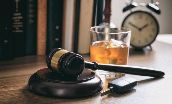 Law gavel, alcohol and car keys on a wooden desk, dark background