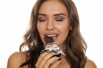 Portrait of beautiful young woman eating cereal bar on white background