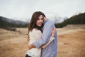 Engaged couple hugging in valley with mountain and forest view in background in Banff National Park