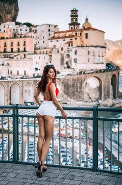 Fashion portrait of a young beautiful girl in red bikini and white shorts in Atrani, Amalfi coast, Italy, Europe