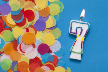 Number 7 celebration candle with party confetti
