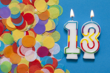 Number 13 celebration candle with party confetti