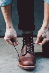 Male tying boot laces outdoors