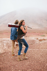 Couple With Guitar Camping in a Wild and Desert Area