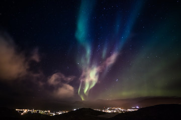 Aurora Borealis with shining stars on the sky over the mountains and highlighted city, Nuuk, Greenland
