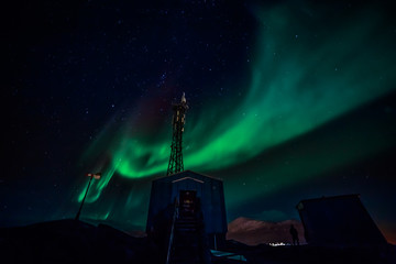 Green waves of Aurora Borealis with shining stars over the mountains and radio tower, Nuuk, Greenland