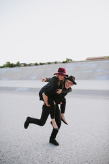Cute couple wearing hats and giving a piggyback ride