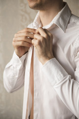 Man's hands buttoning the shirt