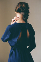 Woman back to camera dressed in navy dress with cut on back