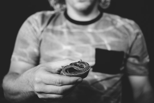 Black and white photo of someone showing a roll of bills