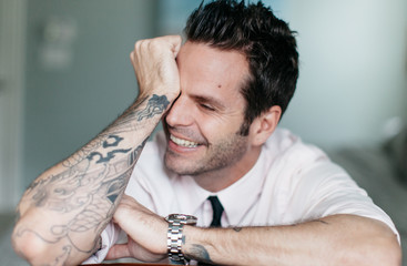 A handsome man with tattoos sitting with his arms on a chair