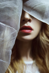 beauty with red lips hiding behind a veil