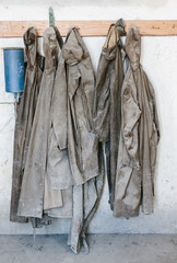 Used and Destroyed waterproof workwear hanging on hangers