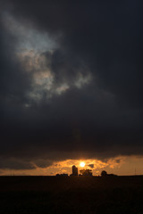 farm buildings and silos are silhouetted by a setting sun