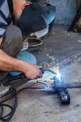 Car mechanic welding car part with torch.