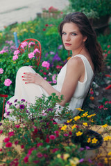 Beautiful young woman in white dress sitting in a garden