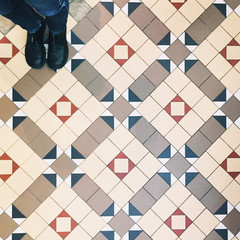 Standing on a multi-coloured tiled floor in London