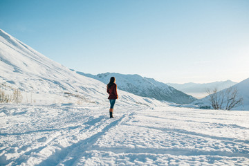 young woman on a snowy trail in the mountains looks ahead