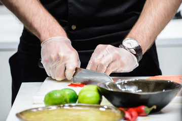 man in a black uniform chef cut vegetables on the table closeup