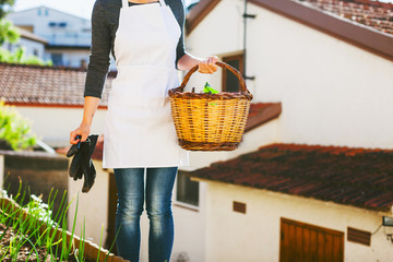 Young woman holding a basket of fresh vegetables in an urban garden.