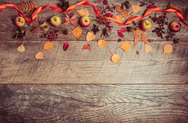 Autumn arrangement of leaves, apples and berries on a wooden background with free space for text. Top view, season concept, toned retro effect