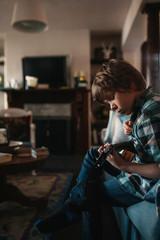 Young boy practising ukulele inside on couch