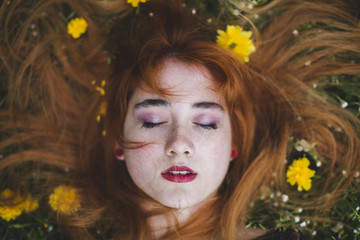 Ginger haired woman laying in flowers
