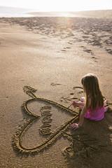Girl writing word mom in sand on beach
