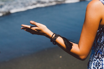 Crop image of woman arm enjoying the summer sunshine  on the black sand beach