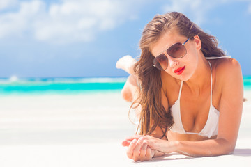 portrait of long haired girl in bikini wearing red lips on tropical barbados beach