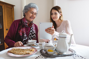 Grandma and Granddaughter Using Tablet Computer while Having a Tea Time